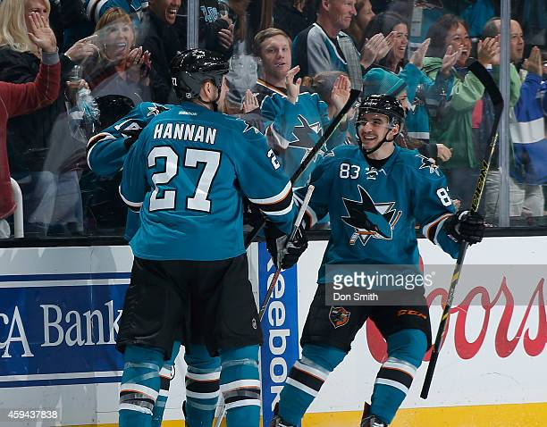 Scott Hannan and Matt Nieto of the San Jose Sharks celebrate a goal against members of the Arizona Coyotes during an NHL game on November 22 2014 at...