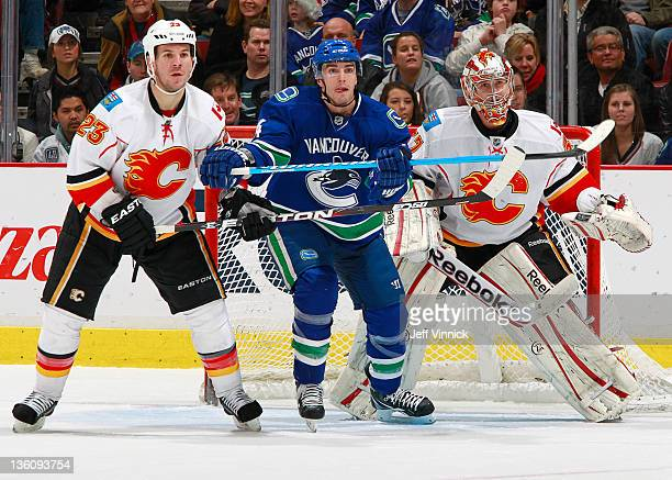Scott Hannan of the Calgary Flames Alex Burrows of the Vancouver Canucks and Leland Irving of the Flames look to the shot during their NHL game at...