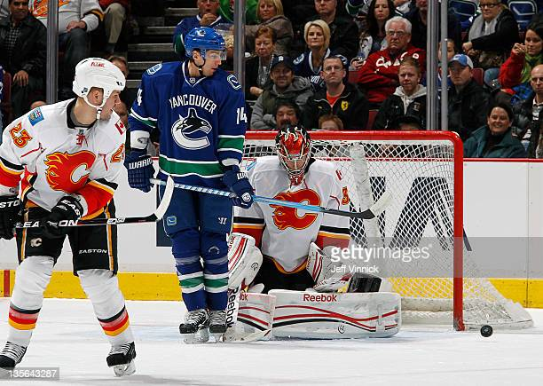 Scott Hannan of the Calgary Flames and Alex Burrows of the Vancouver Canucks look on as Henrik Karlsson of the Calgary Flames makes a save during...