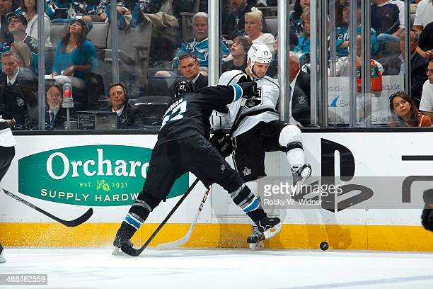 Scott Hannan of the San Jose Sharks checks Kyle Clifford of the Los Angeles Kings into the boards in Game Seven of the First Round of the 2014 NHL...