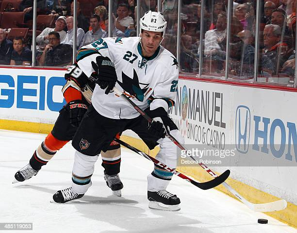 Scott Hannan of the San Jose Sharks handles the puck against Matt Beleskey of the Anaheim Ducks on April 9 2014 at Honda Center in Anaheim California