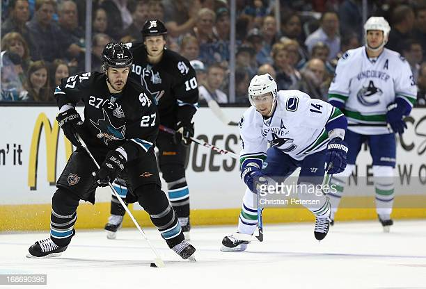 Scott Hannan of the San Jose Sharks skates with the puck ahead of Alex Burrows of the Vancouver Canucks in Game Four of the Western Conference...