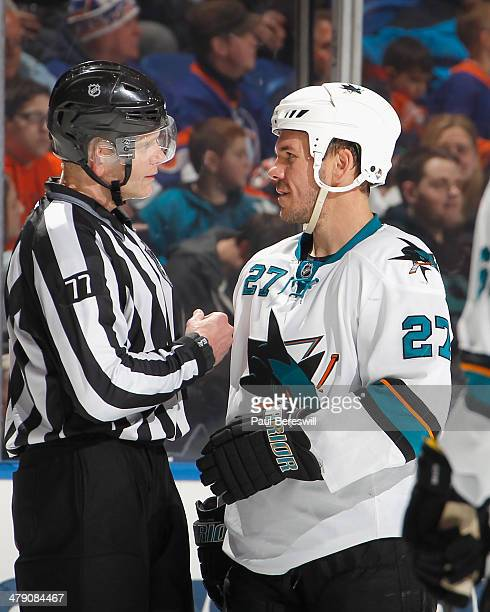 Scott Hannan of the San Jose Sharks talks with linesman Tim Nowak during an NHL hockey game against the New York Islanders at Nassau Veterans...