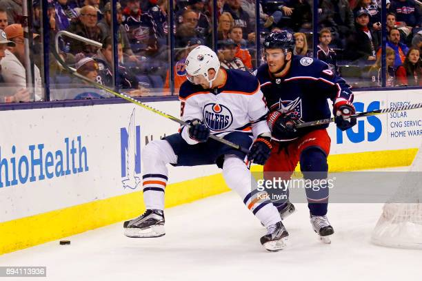 Scott Harrington of the Columbus Blue Jackets and Anton Slepyshev of the Edmonton Oilers battle for control of the puck during the game on December...