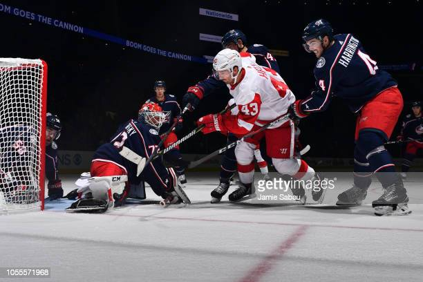 Scott Harrington of the Columbus Blue Jackets defends as Sergei Bobrovsky stops a shot from Darren Helm of the Detroit Red Wings during the second...