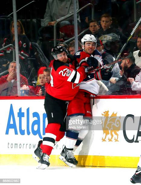 Scott Harrington of the Columbus Blue Jackets is checked into the boards by Stefan Noesen of the New Jersey Devils during the game at Prudential...