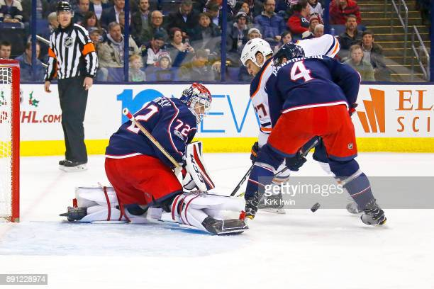 Scott Harrington of the Columbus Blue Jackets looks to clear the rebound as Sergei Bobrovsky of the Columbus Blue Jackets stops a shot from Milan...