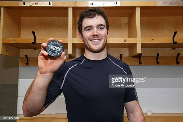 Scott Harrington of the Columbus Blue Jackets poses for photo with the puck with which he scored his first career NHL goal in the locker room after...