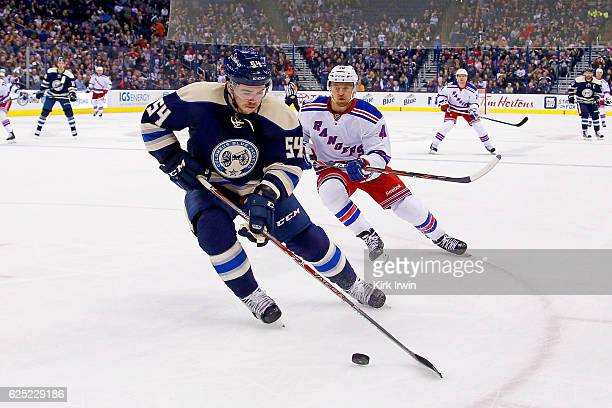 Scott Harrington of the Columbus Blue Jackets skates the puck away from Michael Grabner of the New York Rangers during the game on November 18 2016...