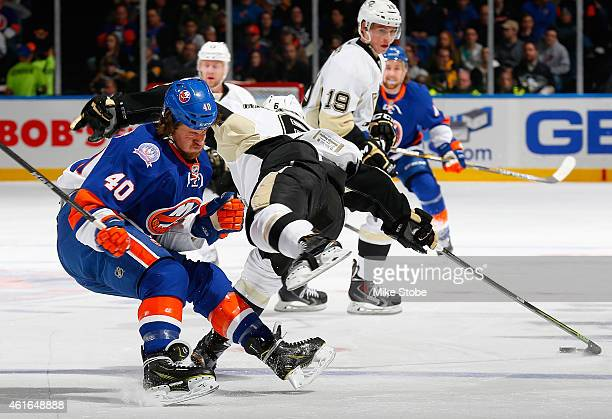 Scott Harrington of the Pittsburgh Penguins collides with Michael Grabner of the New York Islanders at Nassau Veterans Memorial Coliseum on January...
