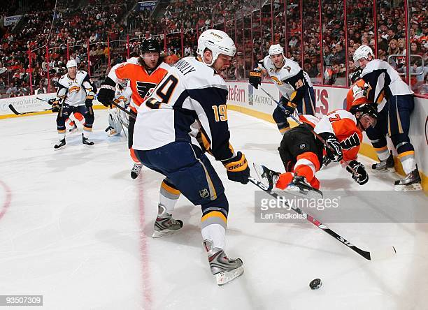 Scott Hartnell and Jeff Carter of the Philadelphia Flyers battles for a loose puck against Tim Connolly and Paul Gaustad of the Buffalo Sabres on...