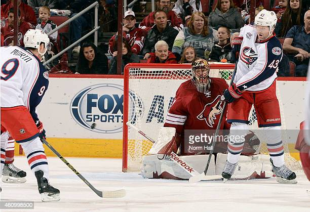 Scott Hartnell of the Columbus Blue Jackets redirects the puck wide of goaltender Mike Smith of the Arizona Coyotes as Jeremy Morin of the Blue...