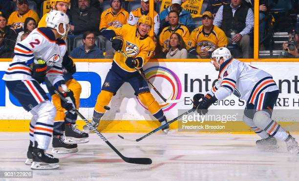 Scott Hartnell of the Nashville Predators passes the puck between Andrej Sekera and Kris Russell of the Edmonton Oilers during the first period at...