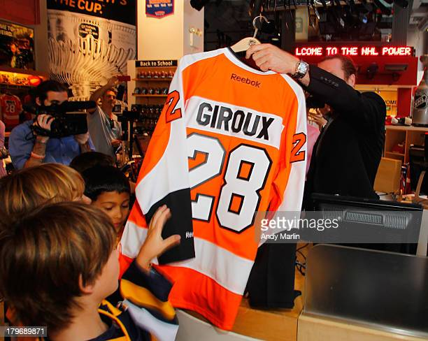 Scott Hartnell of the Philadelphia Flyers holds up a Claude Giroux jersey  that the youth hockey 4dd7a8db9