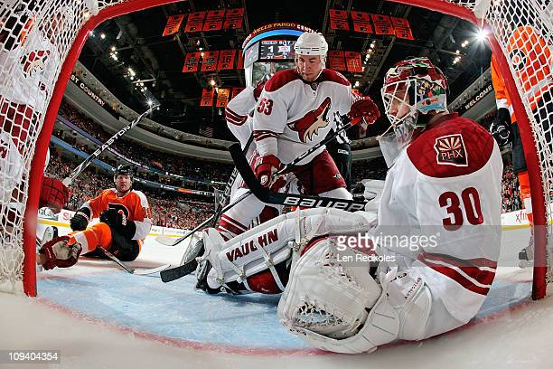 Scott Hartnell of the Philadelphia Flyers looks for the loose puck covered up by Derek Morris and Ilya Bryzgalov of the Phoenix Coyotes on February...
