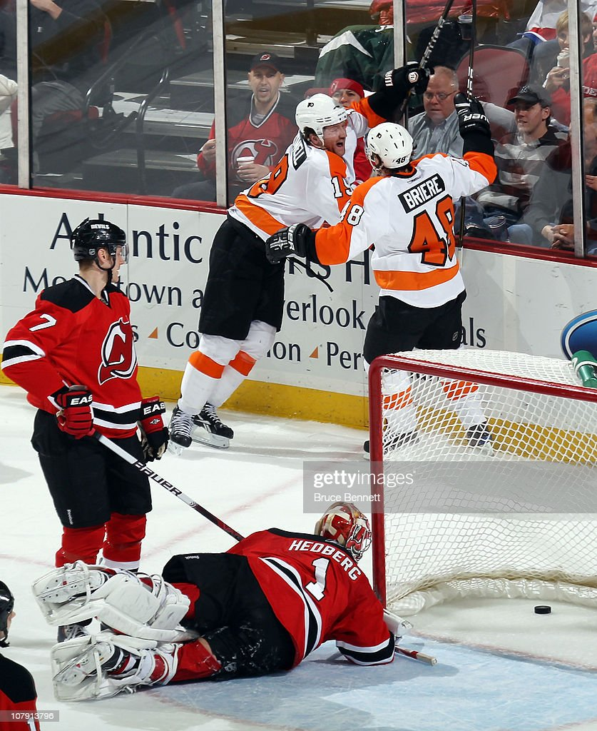 Scott Hartnell #19 of the Philadelphia Flyers scores at 15:46 of the second period against Johan Hedberg #1 of the New Jersey Devils and is joined by Danny Briere #48 at the Prudential Center on January 6, 2011 in Newark, New Jersey.