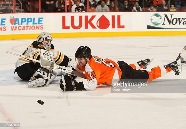 Scott Hartnell of the Philadelphia Flyers slides on the ice after being tripped as goaltender Tim Thomas of the Boston Bruins looks on at the Wells...
