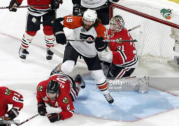 Scott Hartnell of the Philadelphia Flyers steps over a fallen Duncan Keith of the Chicago Blackhhawks as he waits in position in front of Blackhawks...