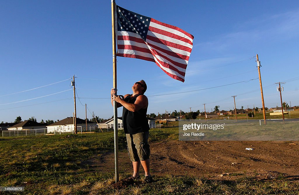 Scott Hasty places an American flag next to where his house was before it was destroyed by the massive tornado that passed through the town one year ago today on May 22, 2012 in Joplin, Missouri. Scott said he was in the house when the EF-5 tornado hit leaving behind a path of destruction along with 161 deaths and hundreds of injuries, but one year later there are signs that the town is beginning to recover.