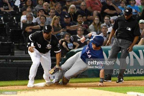 Scott Heineman of the Texas Rangers is tagged out at third base on a steal attempt by Yoan Moncada of the Chicago White Sox during the third inning...