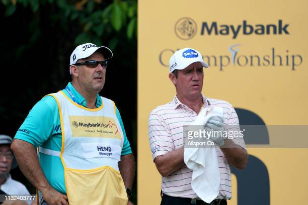 Scott Hend of Australia and his caddie waits on the 6th hole during Day Four of the Maybank Championship at Saujana Golf and Country Club on March 24...