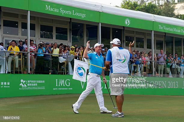 Scott Hend of Australia celebrates his win with his caddie Tony Carolan during round four of the Venetian Macau Open on October 20 2013 at the Macau...