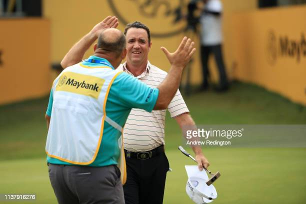 Scott Hend of Australia celebrates with his caddie after his putt after he wins the play off match against Nacho Elvira of Spain during Day Four of...