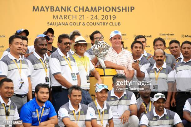 Scott Hend of Australia holds the trophy with the volunteers after he wins the play off match against Nacho Elvira of Spain during Day Four of the...