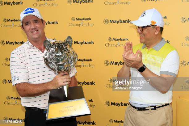 Scott Hend of Australia is given the trophy after he wins the play off match against Nacho Elvira of Spain during Day Four of the Maybank...