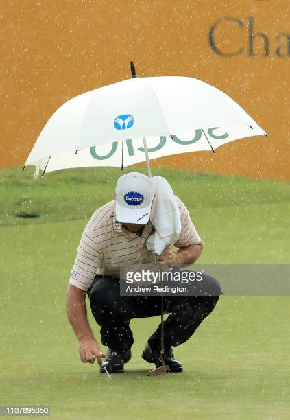 Scott Hend of Australia marks his ball on the 18th green ahead of play being suspended due to bad weather during Day Four of the Maybank Championship...