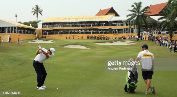 Scott Hend of Australia plays his shot on the first play off match against Nacho Elvira of Spain during Day Four of the Maybank Championship at...
