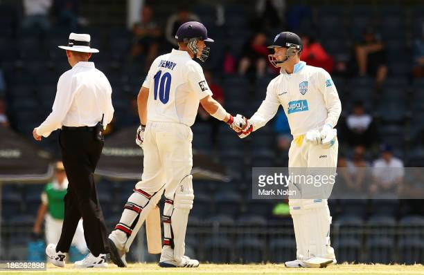 Scott Henry congratulates Michael Clarke after he scored a half century during day one of the Sheffield Shield match between the New South Wales...
