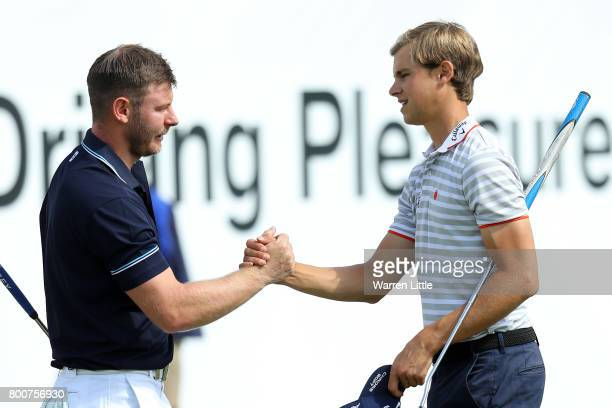 Scott Henry of Scotland shakes hands with Thomas Detry of Belgium on the 18th green during the final round of the BMW International Open at Golfclub...