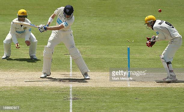 Scott Henry of the Blues is bowled by Ashton Agar of the Warriors during day two of the Sheffield Shield match between the New South Wales Blues and...
