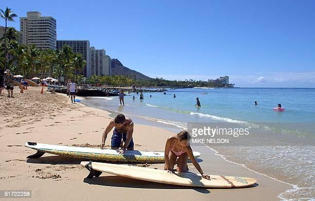Scott Herson and Marilyn Shepard of Manhattan Beach California wax their surfboards 06 September 2001 on Waikiki Beach in Hawaii near where sharks...