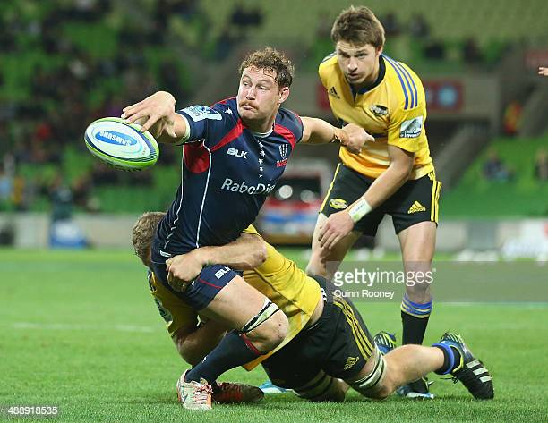 Scott Higginbotham of the Rebels passes the ball whilst being tackled during the round 13 Super Rugby match between the Rebels and the Hurricanes at...