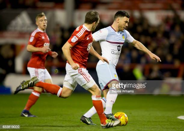 Scott Hogan of Aston Villa is challenged by David Vaughan of Nottingham Forest during the Sky Bet Championship match between Nottingham Forest and...