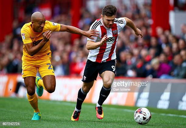 Scott Hogan of Brentford battles for the ball with Alex JohnBaptiste of Preston North End during the Sky Bet Championship match between Brentford and...