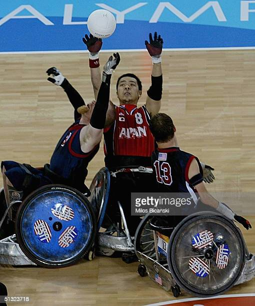 Scott Hogsett and Clifton Chunn of USA fight for a ball with Hiroyuki Misaka of Japan during the Wheelchair Rugby mach between USA and Japan at the...