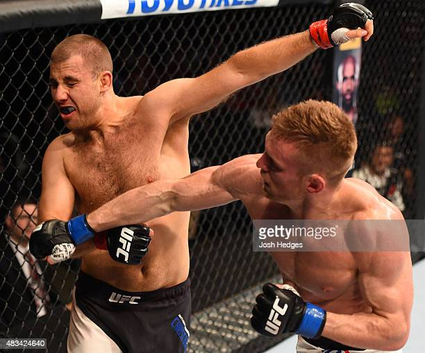 Scott Holtzman punches Anthony Christodoulou of Greece in their lightweight bout during the UFC Fight Night event at Bridgestone Arena on August 8...