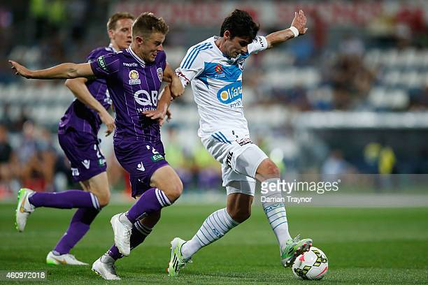 Scott Jamieson of Perth Glory holds onto Gui Finkler of Melbourne Victory to give away a penalty during the round 14 ALeague match between the...