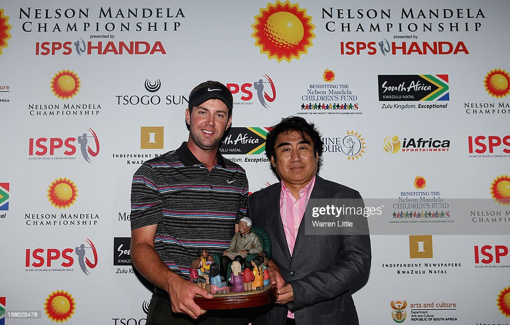 Scott Jamieson of Scotland is awarded the trophy by Haruhisa Handa, Chairman of ISPS Handa after winning The Nelson Mandela Championship presented by ISPS Handa in a three way play-off against Steve Webster of England and Eduardo de la Riva of Spain at Royal Durban Golf Club on December 9, 2012 in Durban, South Africa.