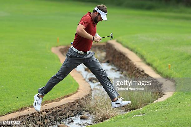 Scott Jamieson of Scotland jumps over a stream on the 1st hole during the second round of the Alfred Dunhill Championship at Leopard Creek Country...
