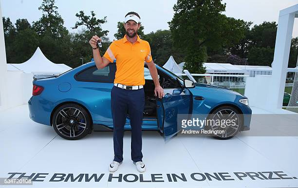Scott Jamieson of Scotland poses with his new BMW M2 car after his holeinone on the 10th during day two of the BMW PGA Championship at Wentworth on...