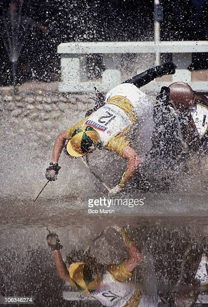 Scott Keach of Australia falls from his mount Trade Commission and into the water during the Cross Country section of the Three Day Event Competition...