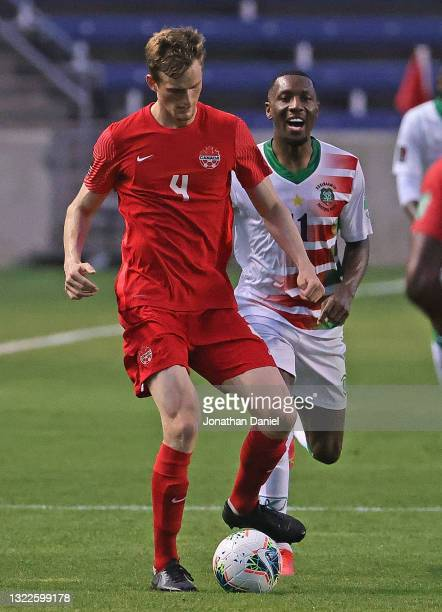 Scott Kennedy of Canada advances the ball in front of Sheraldo Becker of Suriname during a FIFA World Cup Qualifier at SeatGeek Stadium on June 08,...