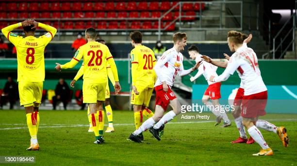Scott Kennedy of Jahn Regensburg celebrates with team mates after scoring their side's first goal during the DFB Cup Round of Sixteen match between...