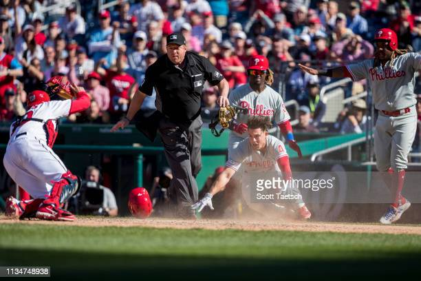 Scott Kingery of the Philadelphia Phillies beats the tag by Kurt Suzuki of the Washington Nationals to score during the eighth inning at Nationals...