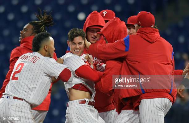 Scott Kingery of the Philadelphia Phillies gets congratulated by JP Crawford and other teammates after a walk off sacrifice fly in the twelfth inning...