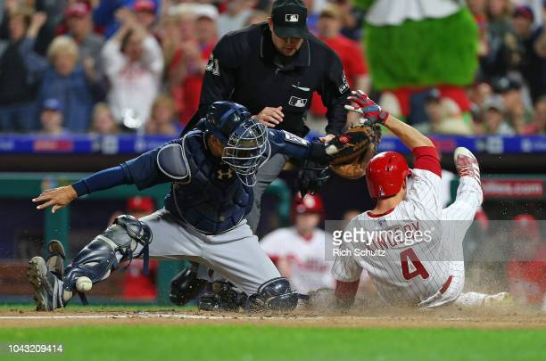 Scott Kingery of the Philadelphia Phillies scores as catcher Kurt Suzuki of the Atlanta Braves can't handle the throw on a tworun single by Cesar...